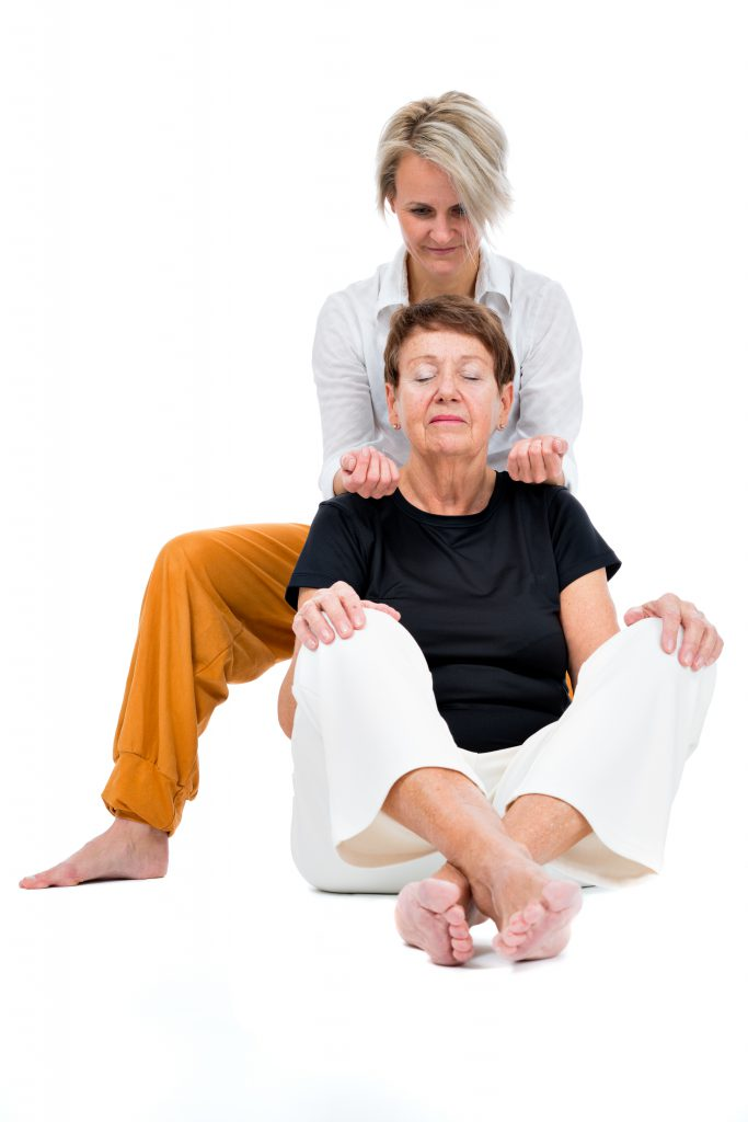 senior woman receiving thai massage from female thaimassager